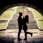 Couple of lovers hugging under a bridge on a rainy day - Silhouettes of man and woman on a romantic date under the rain, laughing and having fun