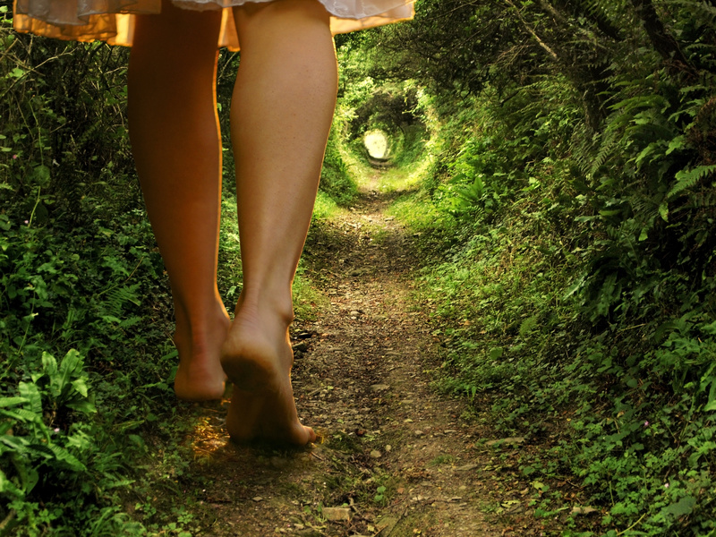 A collage of two images showing giant female legs walking onto a tunnel-like forest path with light at the end