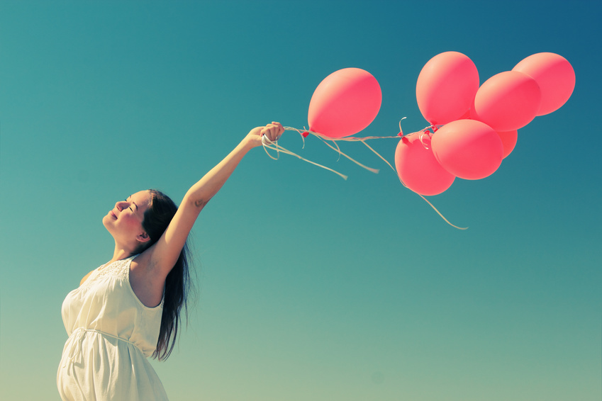 young woman holding red balloons